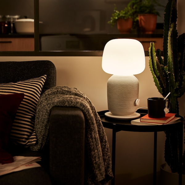 A white table lamp with WiFi speaker on a coffee table, with a coffee cup and some books, beside the edge of a sofa.