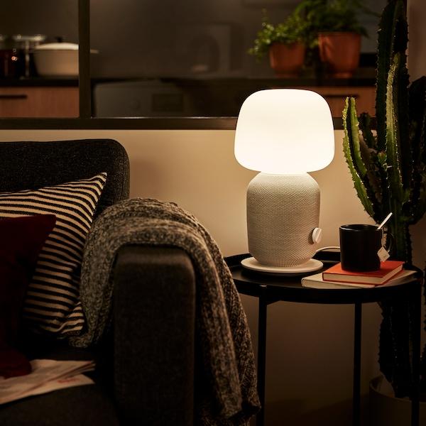 Eine weiße SYMFONISK Tischleuchte mit WiFi-Speaker auf einem Couchtisch mit einer Kaffeetasse und ein paar Büchern. Daneben ist ein Sofa zu sehen.