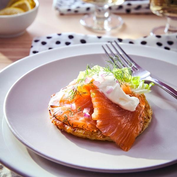 Egy tányéron felszolgált kis méretű szendvics hidegen füstölt lazaccal.