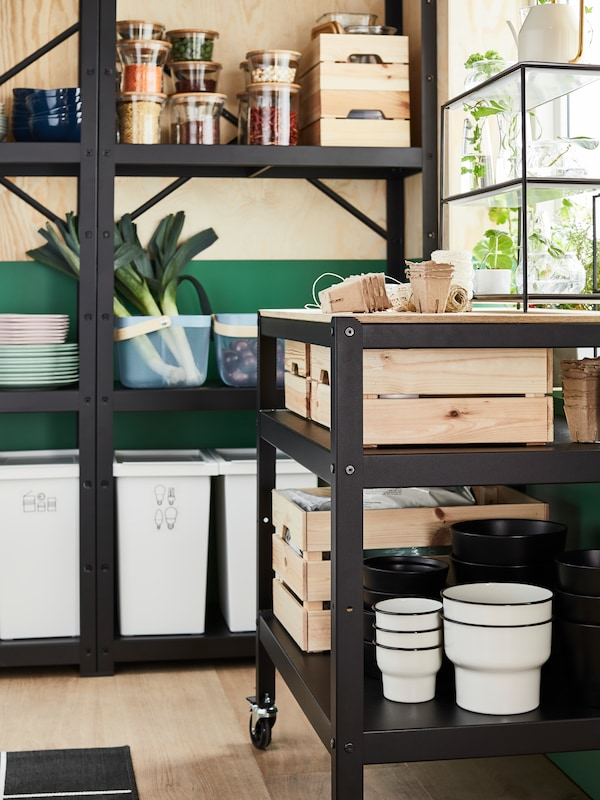 A black kitchen cart and a black open shelving unit storing various items such as dry goods, leeks and pine boxes.