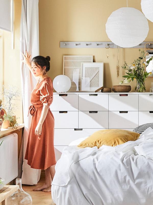 Uma mulher olha pela janela de um quarto. Atrás dela, encontram-se duas cómodas NORDLI, alguns candeeiros e uma cama.