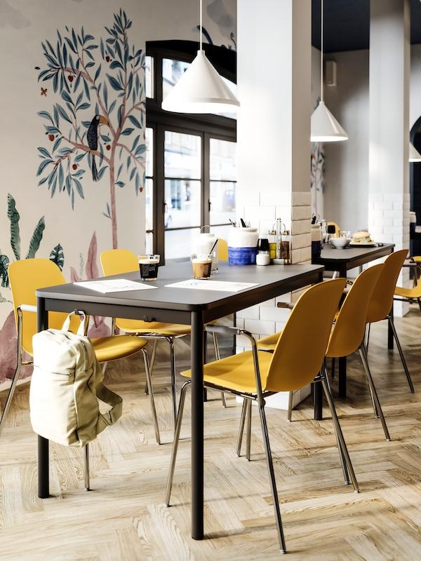 Tavolo da pranzo con ganci sui lati, dove è appeso uno zaino beige. Sedie giallo scuro, lampade a sospensione bianche, parete con disegno decorativo.