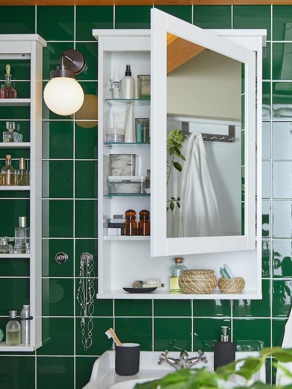 O baie cu gresie verde cu o aplică FRIHULT și un dulap oglindă HEMNES deschis, în care se văd produse de înfrumusețare.