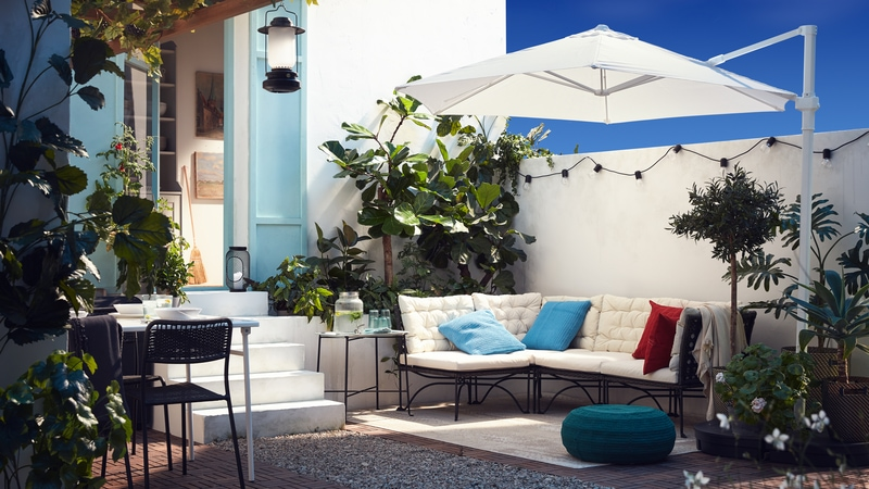 A patio with outdoor sofa and a smaller white table and stools, a dining table with chairs and a parasol.
