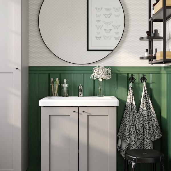 Un espello redondo negro grande sobre un lavabo branco con dúas portas de armarios grises debaixo, fronte a un panel de parede verde.