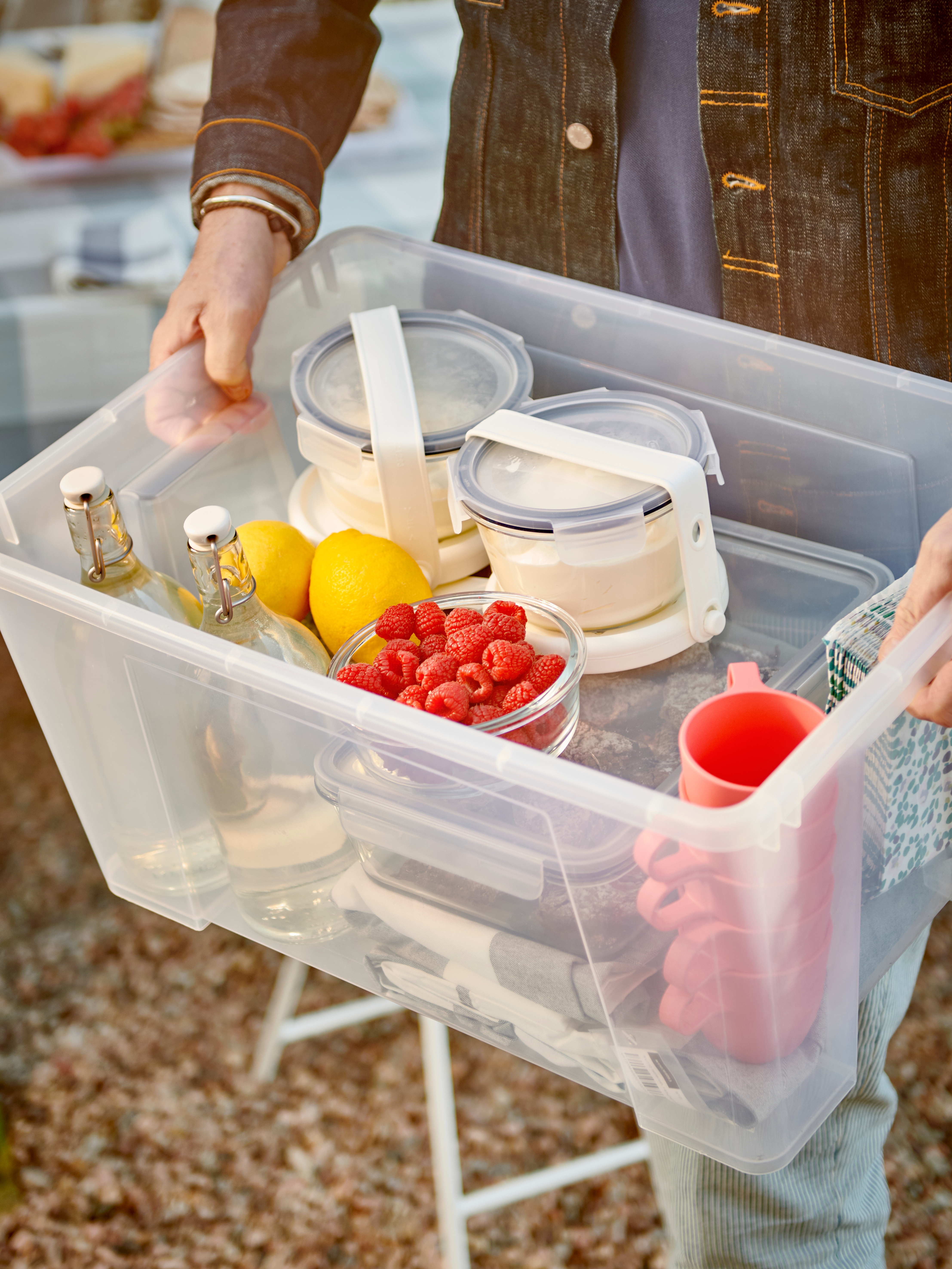 Hands hold a transparent SAMLA box filled with tableware, glass bottles and food containers strapped to ice packs.