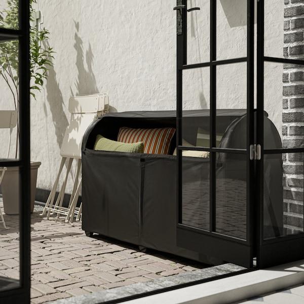 Stor, sort udendørs opbevaringsboks med grønne og orange puder op ad en hvid mur ved siden af en åben glasdør.