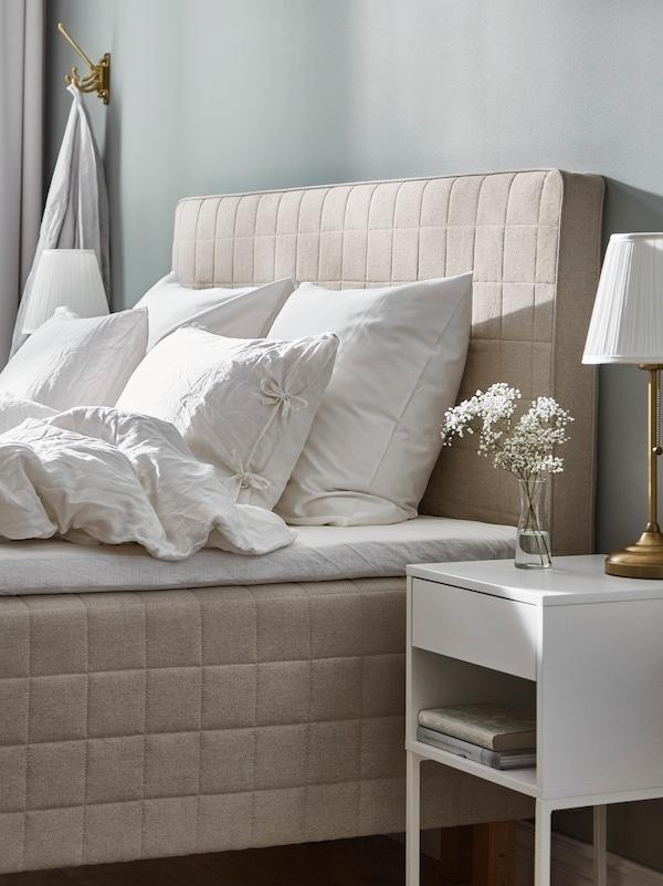 غرفة نوم بها مرتبة STUVLAND مع لوح رأس، وطاولة سرير جانبية VIKHAMMER مع كتابين ومصباح ومزهرية بها زهور.