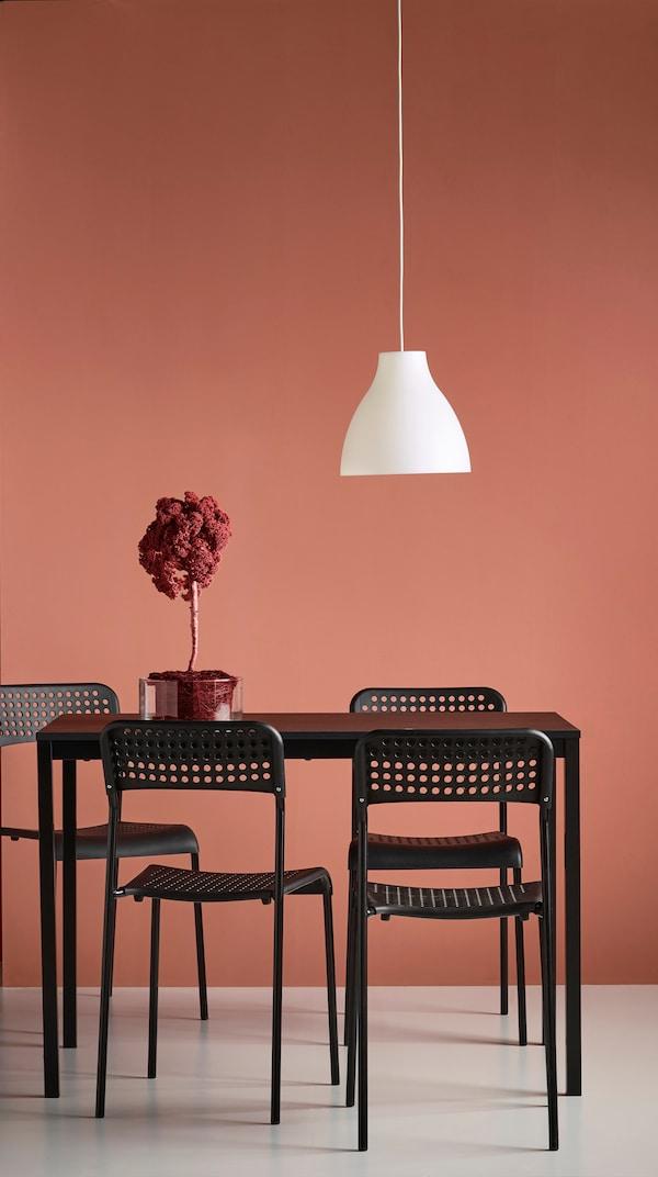 Stôl so stoličkami v čiernej farbe a závesná lampa.