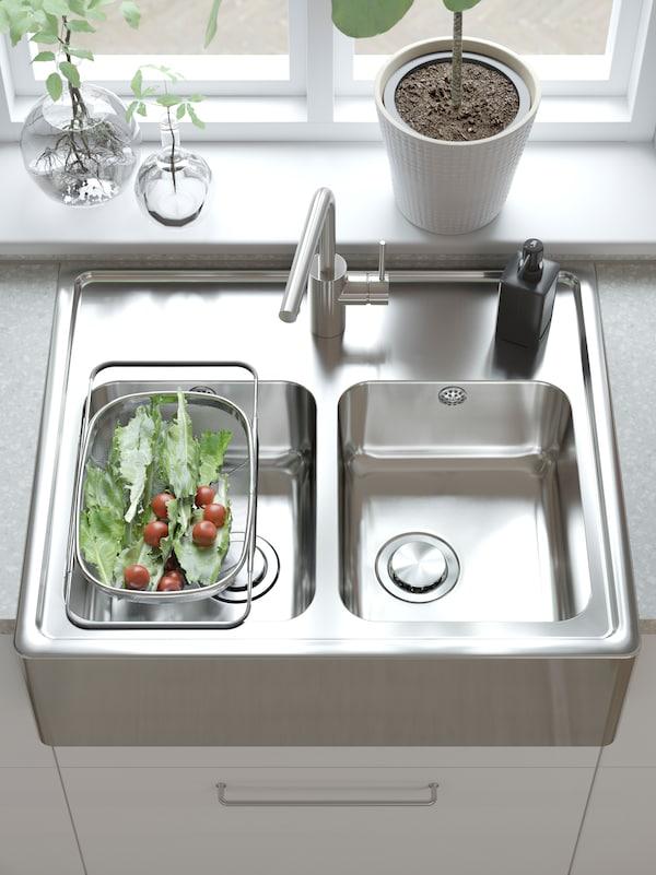 Prikaz kuhinjske radne ploče na kojoj se nalazi IKEA BREDSJÖN sudoper od nehrđajućeg čelika s dva bazena i vidljivom frontom.