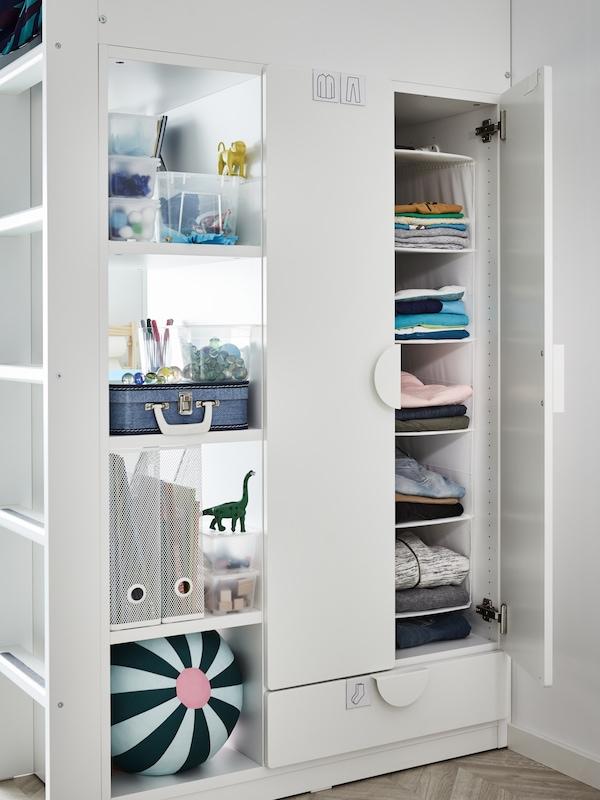 Indbygget garderobeskab ved siden af loftsengen med tøj, der er lagt sammen, bag døre og bokse med ting på hylderne.
