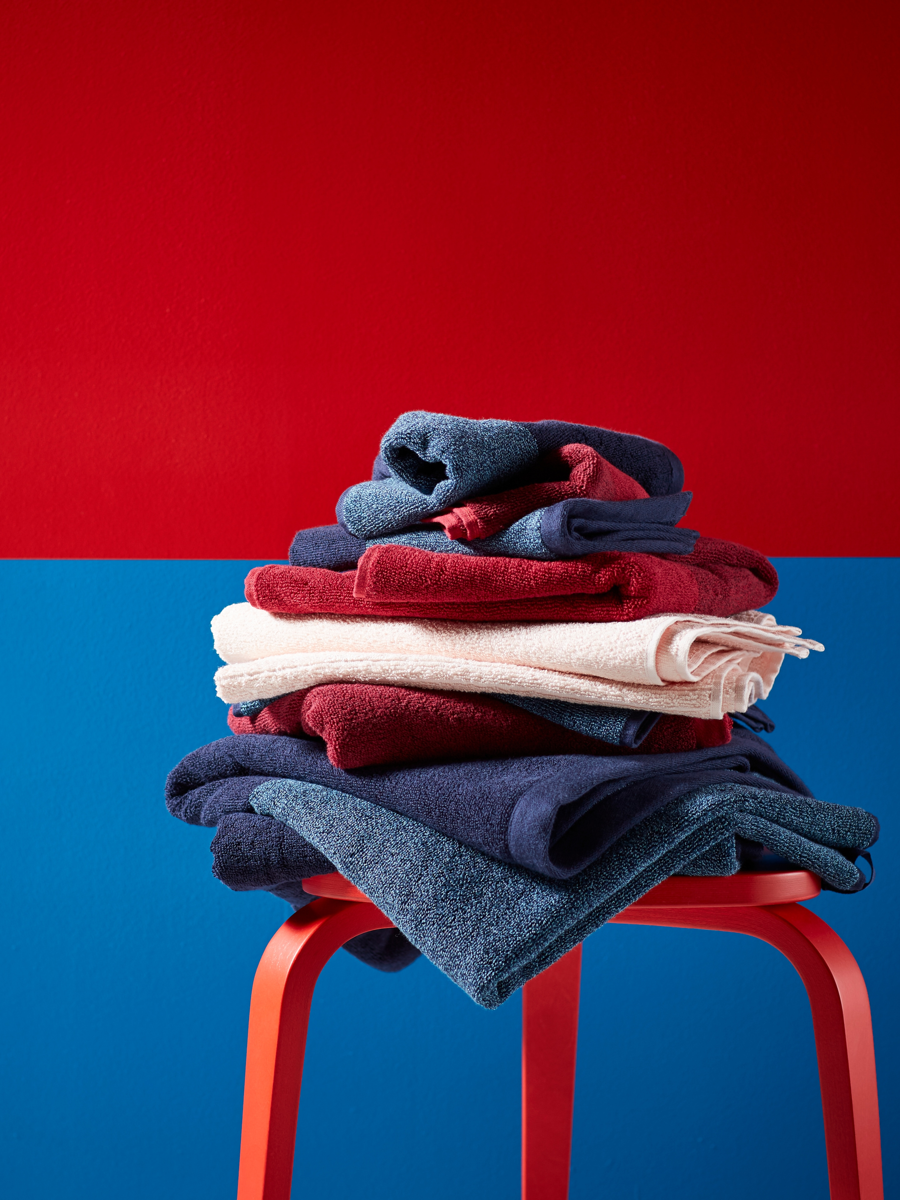 A selection of HIMLEÅN bath towels of different colors, stacked on a red wooden stool against a blue and red background.