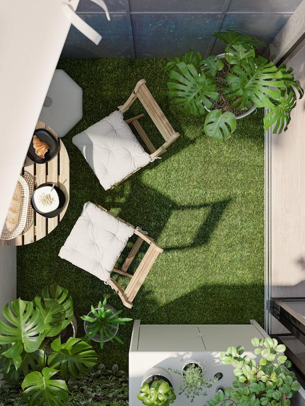 Ein Balkon mit Bodenbelag aus Kunstgras, zwei Klappstühlen und einem kleinen Tisch mit Frühstück darauf.