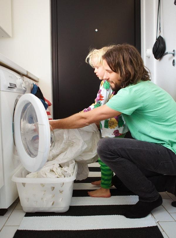 En far og søn tager rent vasketøj ud af en vaskemaskine og putter det i  BLASKA vasketøjskurv.