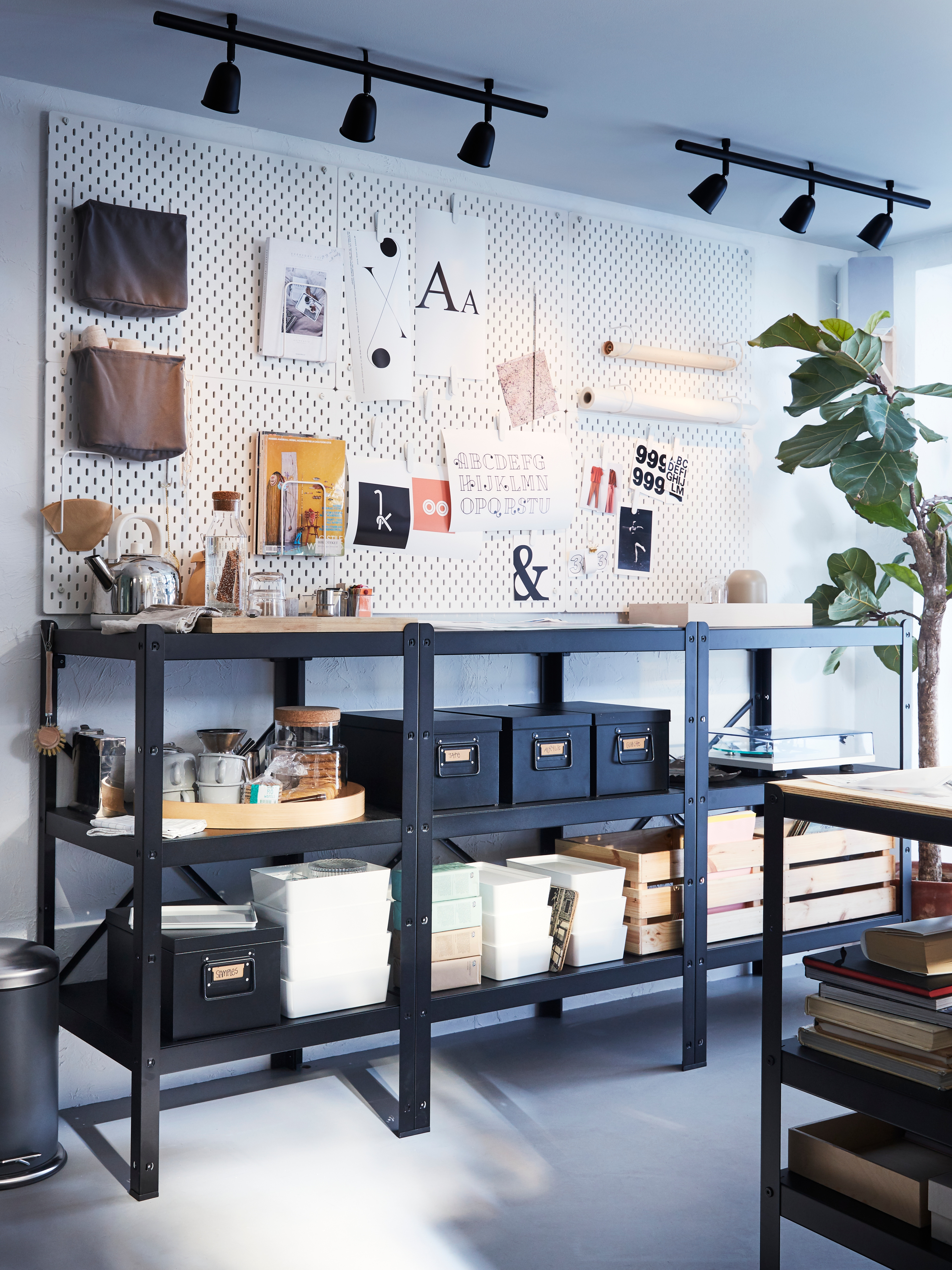A room with a BROR shelving unit in black, holding boxes and various items, in front of a wall with a pegboard with notes.