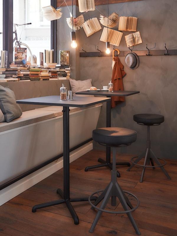 Pred oknom stoja dva štvorcové stoly s háčikmi, lavica so sivými vankúšmi a dve čierne stoličky na aktívne sedenie a státie.