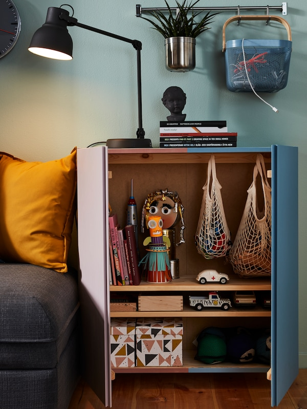 An open cabinet in a living room revealing two net bags, several small boxes and toys.