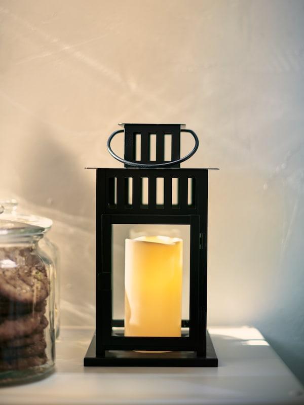 Une lanterne BORRBY noire avec une bougie bloc à DEL blanche. La lanterne est posée sur une surface blanche devant un mur blanc.