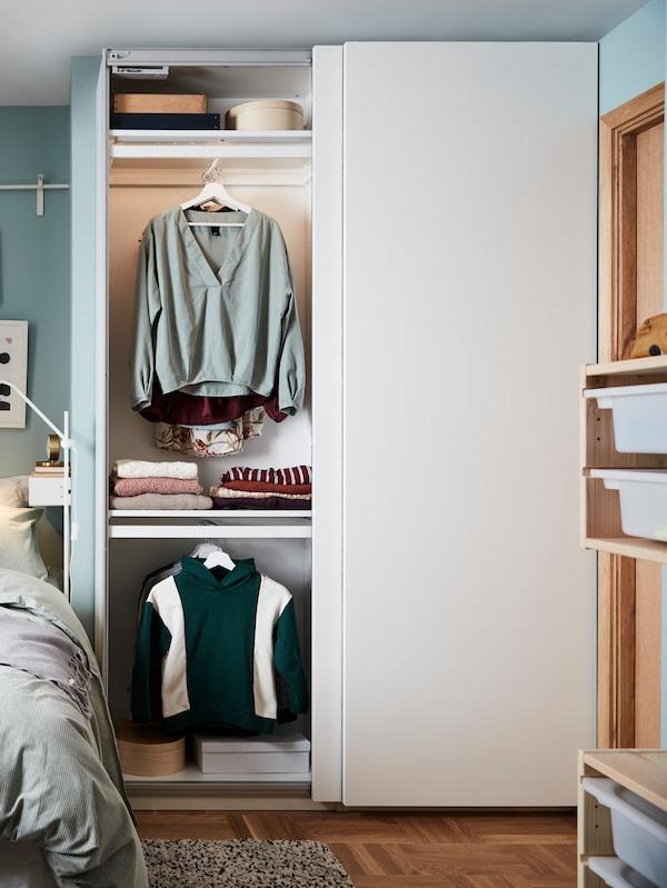 У стены стоит комбинация для хранения ОПХУС с белыми дверцами ФОННЕС и встроенным местом для отдыха.