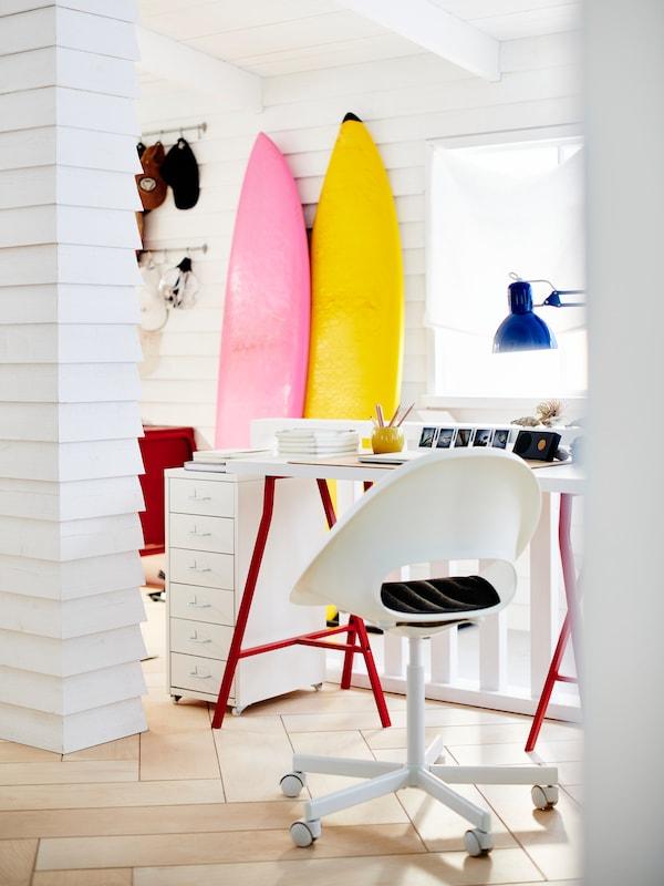Un bureau rouge et blanc avec une chaise pivotante blanche, une lampe bleue, et des planches de surf rose et jaune contre le mur du fond.