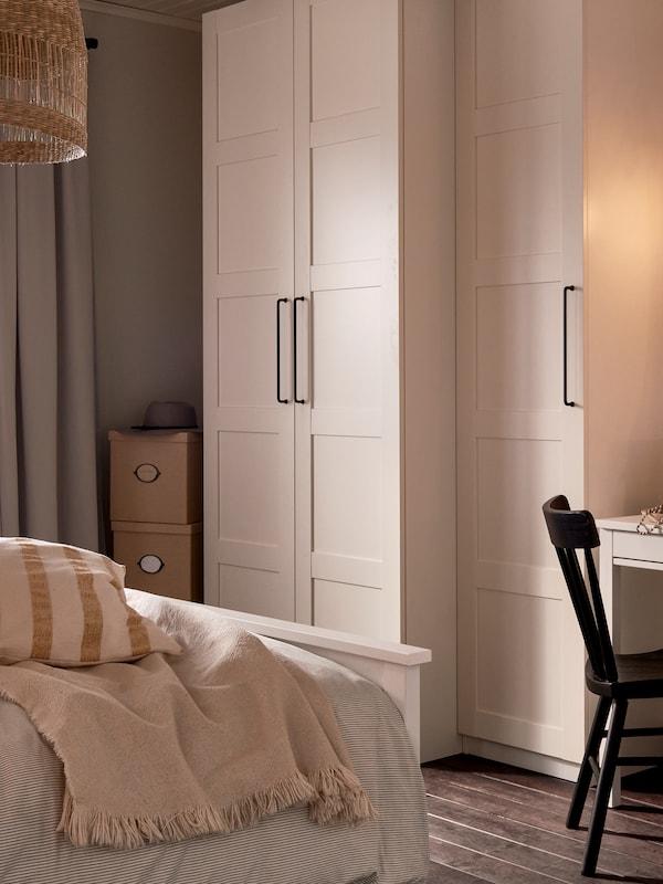 Un armario PAX blanco con puertas BERGSBO a los pies de una cama HEMNES blanca y una silla NORRARYD negra.
