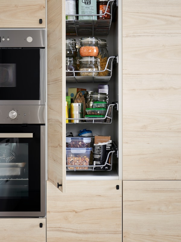 A tall cabinet in a kitchen with an open light ash effect door showing wire baskets, food containers and more.