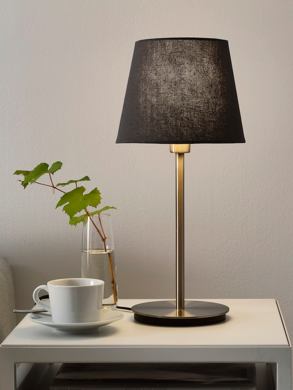 A single table lamp standing on a table with a coffee cup and a glass with a plant bloom in it.