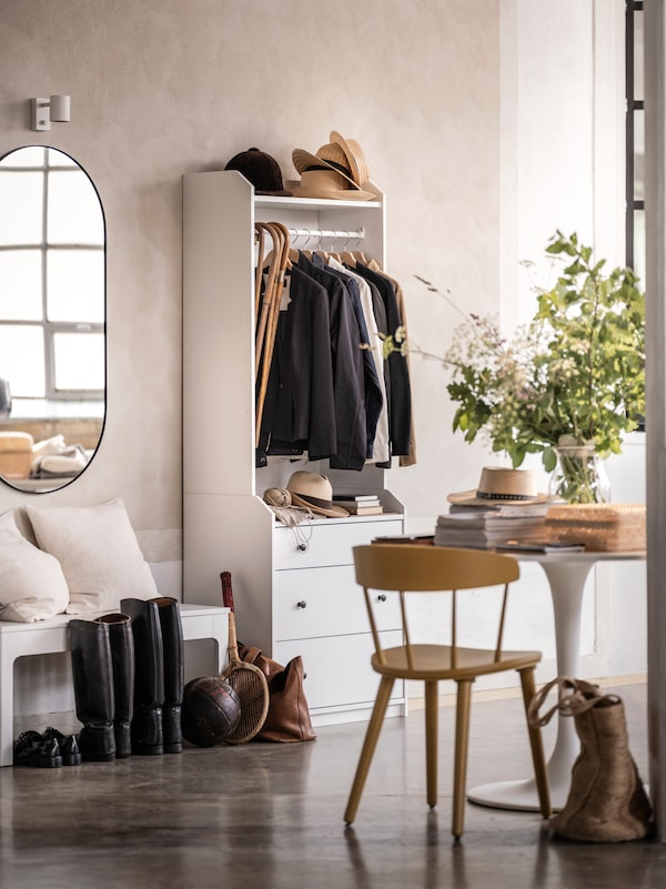 A hallway with a HAUGA open wardrobe with jackets, hats and coats. A LINDBYN mirror is on the wall nearby.