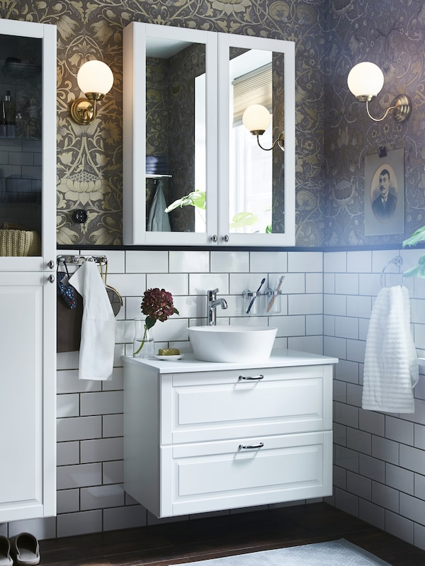 A mirror cabinet on a gold/brown wallpaper/white-tiled wall, a white wash-stand with two drawers and a white high cabinet.