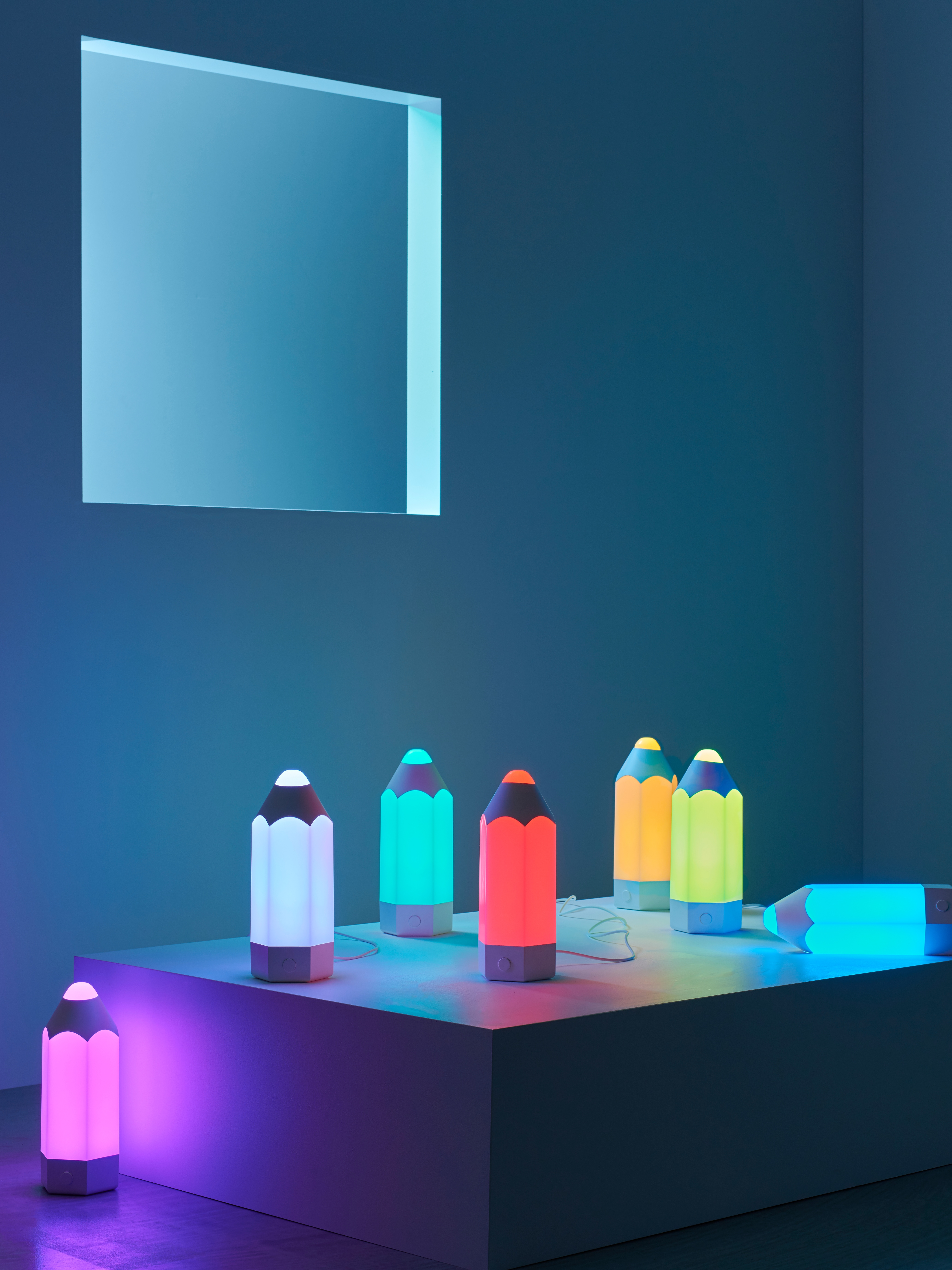A selection of PELARBOJ table lamps in different colors, on display against a blue background with window opening.