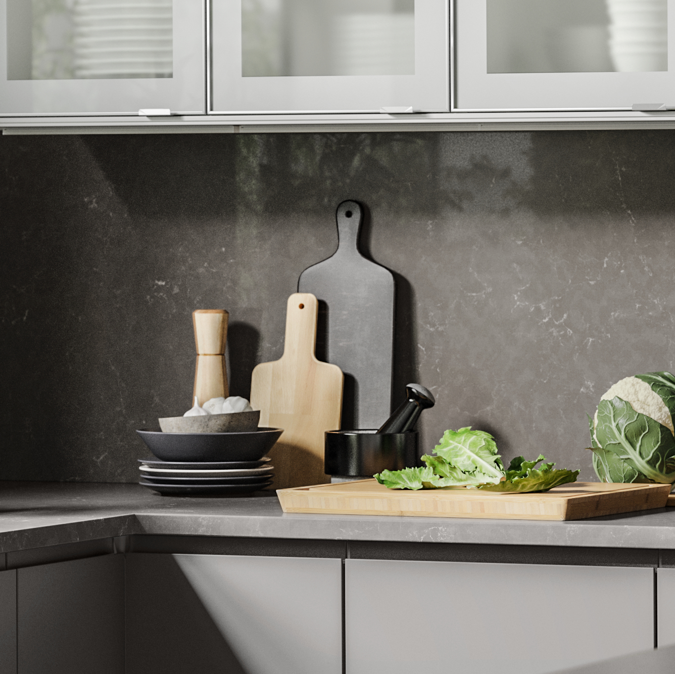 A black marbled effect splasback with two cutting boards leaning on it, and a chopping board with veggies on the worktop.