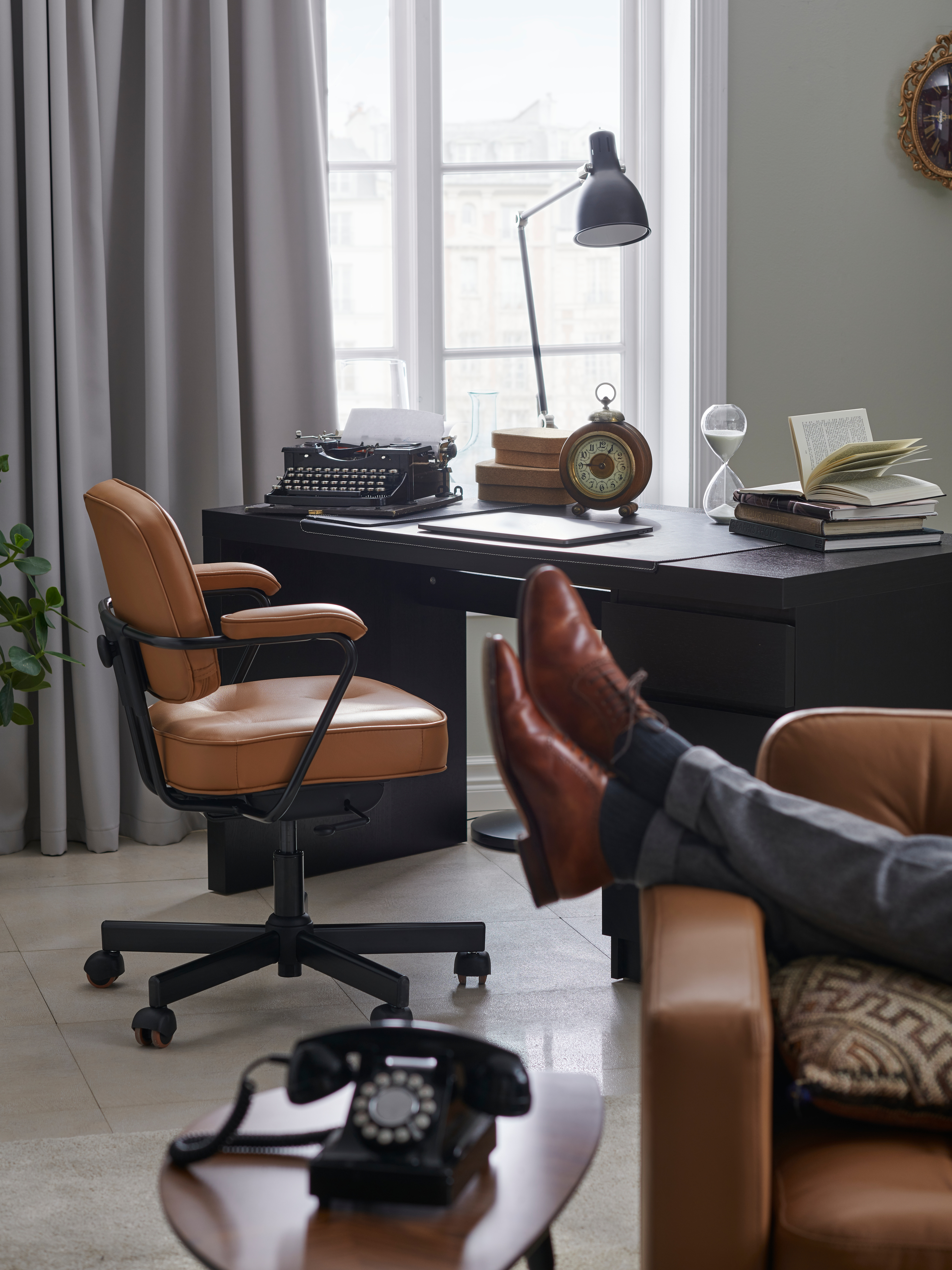 A pair of legs are partially visible on a sofa in the foreground by a leather office chair and black-brown MALM desk.