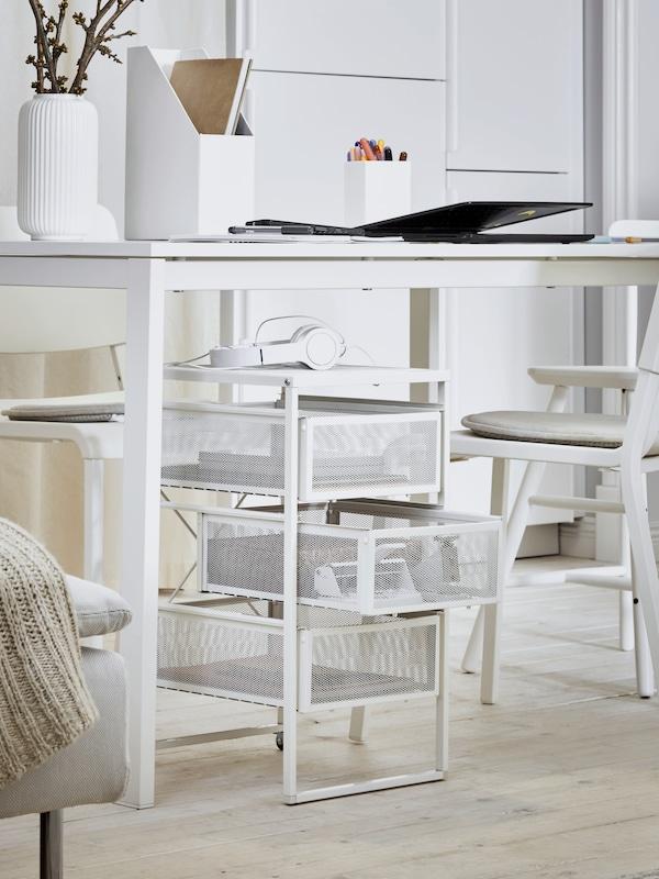 Ein weißer Schreibtisch mit diversen Gegenständen, u. a. einem Computer, einem Zeitschriftensammler und einer weißen Vase mit Zweigen auf der Tischplatte; darunter befindet sich ein weißes Schubladenelement und davor steht ein weißer Stuhl.