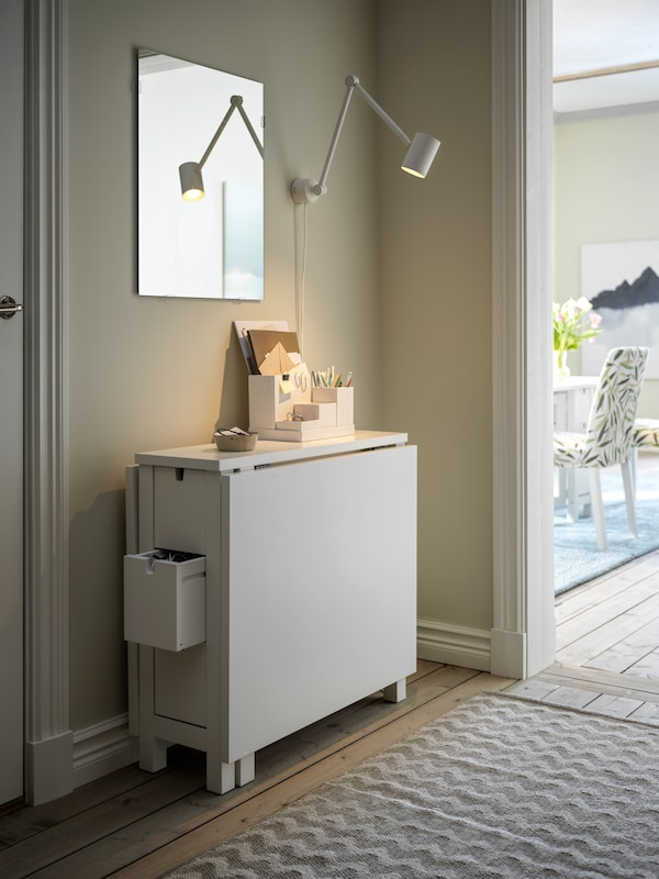 A hallway with a folded-down, white NORDEN gateleg table against a wall, and a LÄRBRO mirror a white NYMÅNE lamp above it.