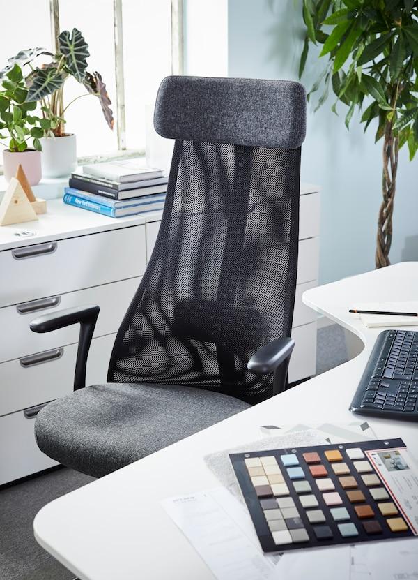 Scrivania angolare bianca BEKANT e una sedia da ufficio girevole nera con schienale in rete davanti a due cassettiere su cui sono appoggiate alcune piante e una pila di libri; sullo sfondo, una finestra.