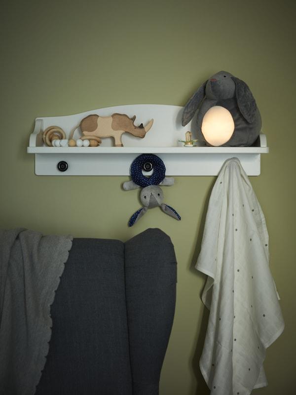 En hvid væghylde, trælegetøj, en grå kanin/batteridrevet tøjdyr med LED-natlampe og en stofble med prikker.
