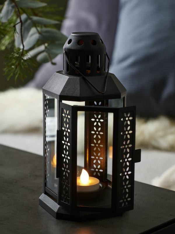 Lanterna ENRUM nera con all'interno una candela GODAFTON accesa