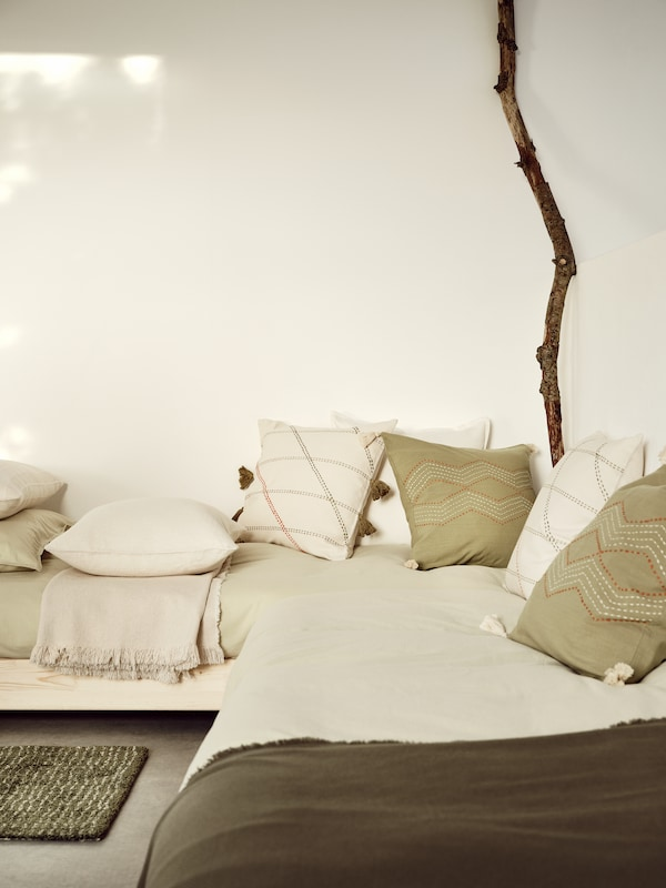 In the corner of a room, a cosy day bed is scattered with HERVOR and HALLVI cushion covers in off-white and green.