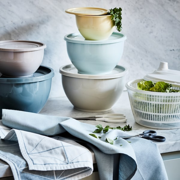 Plastic bowls with lids in soft colours stacked on a counter with tea towels, next to a salad spinner filled with lettuce.