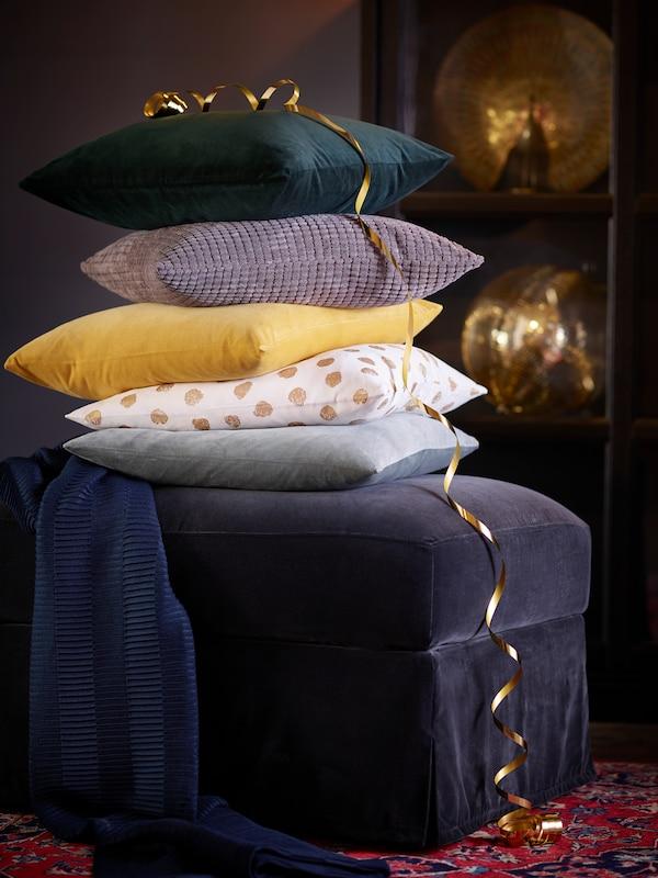 Some cushions stacked on a dark grey FÄRLÖV footstool.