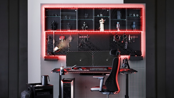 A gaming set-up with UPPSPEL desk and MATCHSPEL chair in the center. The storage on the wall is framed by red led lights.
