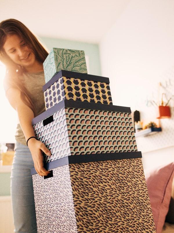 O stivă de patru cutii de depozitare TJENA de diferite mărimi și modele, cea mai mare aflată la partea de jos, este ridicată de o adolescentă.