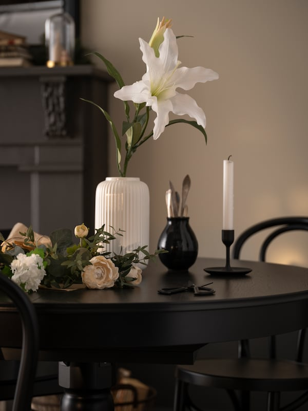 A black dining table decorated with a vase holding a large, white artifical flower.