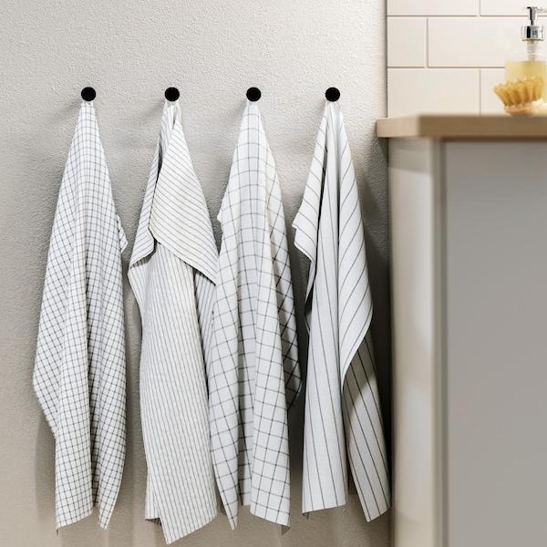 Štyri bielo-tmavosivé vzorované utierky RINNIG zavesené vedľa seba na vešiakoch vedľa kuchynskej pracovnej dosky.
