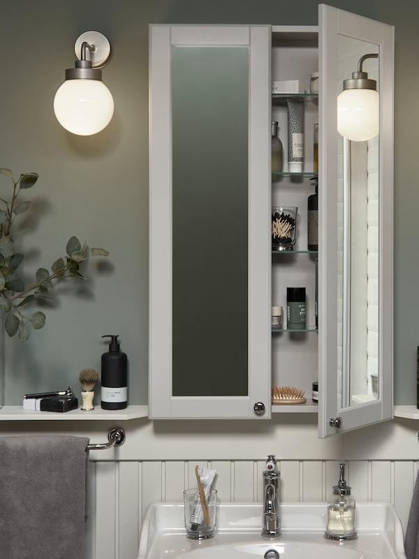 Une armoire à miroir, haute et peu profonde, au-dessus d'un lavabo blanc. Une porte ouverte, articles de toilette visibles à l'intérieur.