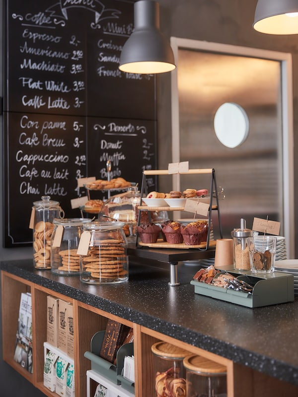 The counter of a cafe, lots of food items displayed on it, storage beneath and a blackboard with writing behind.