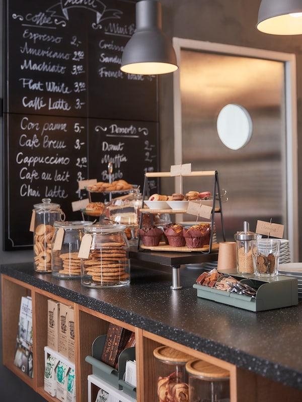 Pult v kavarni, z veliko razstavljenimi živili, prostor za shranjevanje pod pultom in popisana tabla v ozadju.