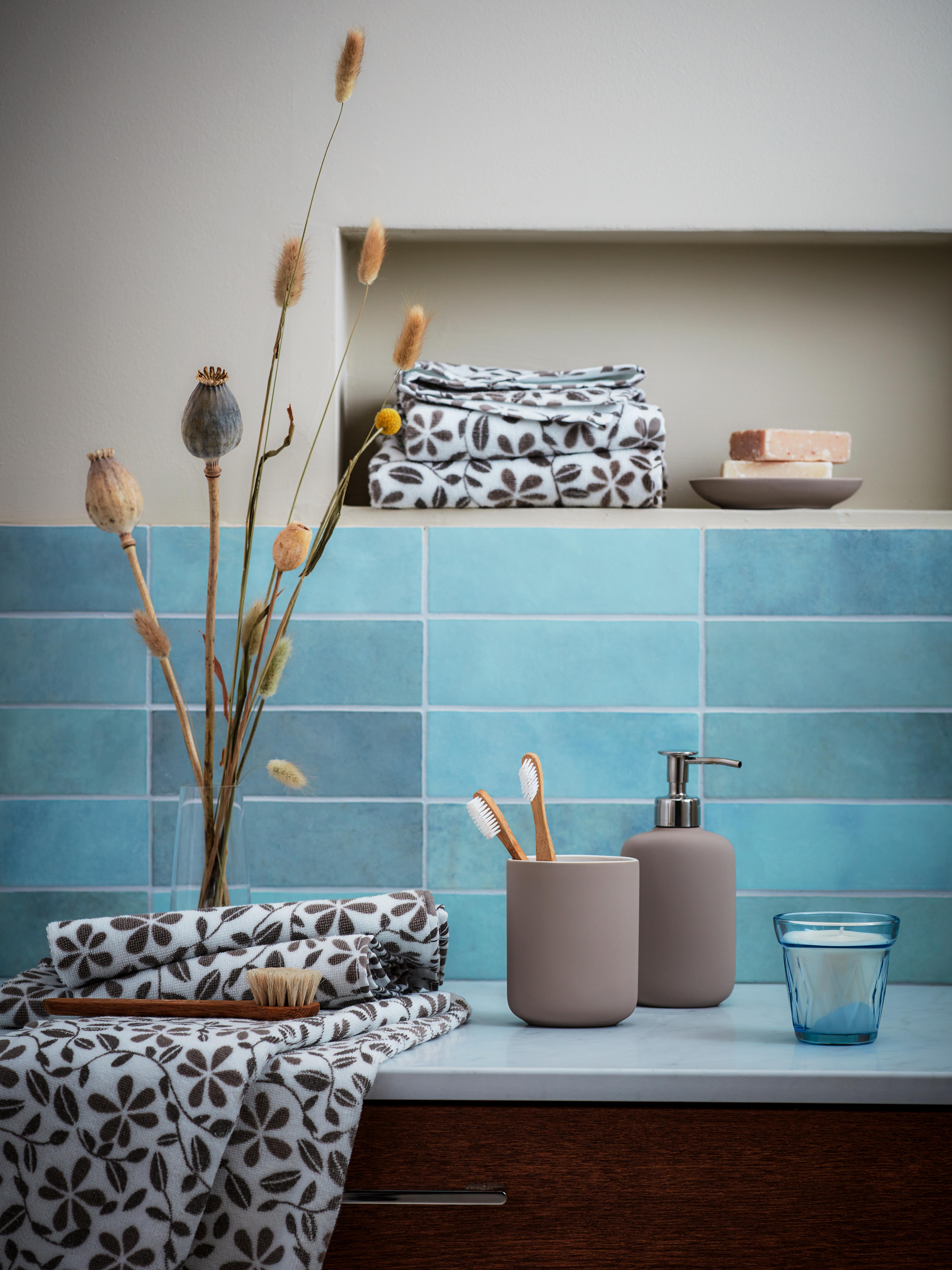 Kupaonica s plavim pločicama s EKOLN dozatorom sapuna i držačem četkica za zube okružen JUVELBLOMMA ručnicima i ukrasima.