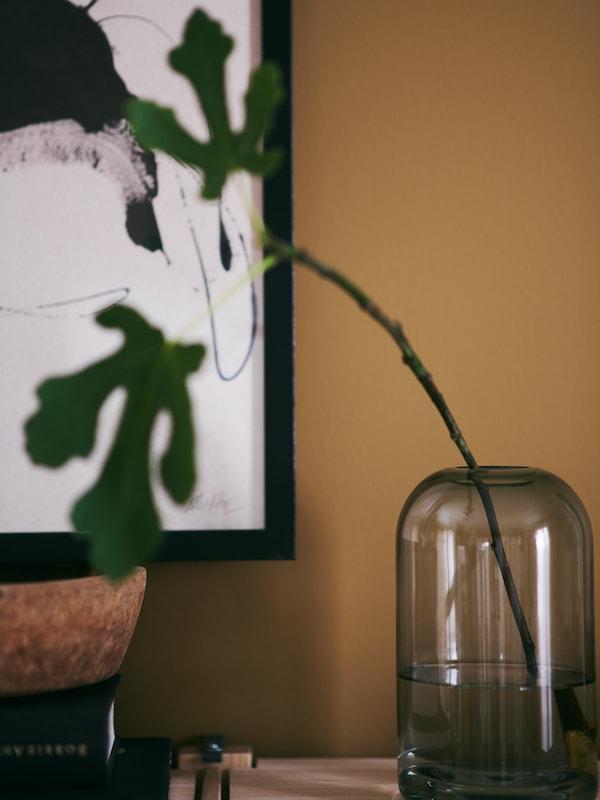 Vase en verre DRÖMSK garni d'une tige de figuier pour une touche de verdure zen.