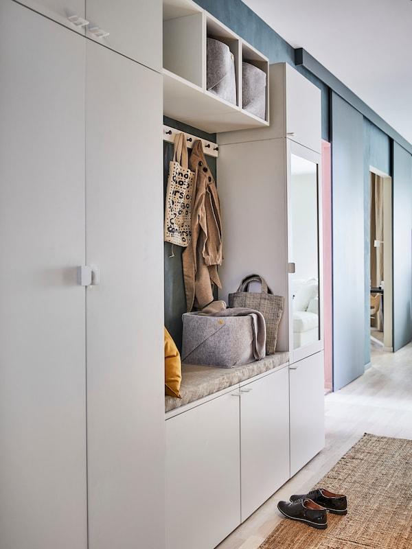 Kombinasi storan PLATSA dengan pintu FONNES berwarna putih dan tempat duduk terbina dalam, terletak bersandar pada dinding.